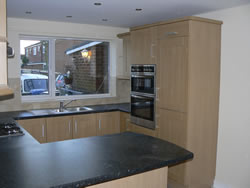 An oak shaker contempary kitchen was installed. The view shows the eye level oven housing.